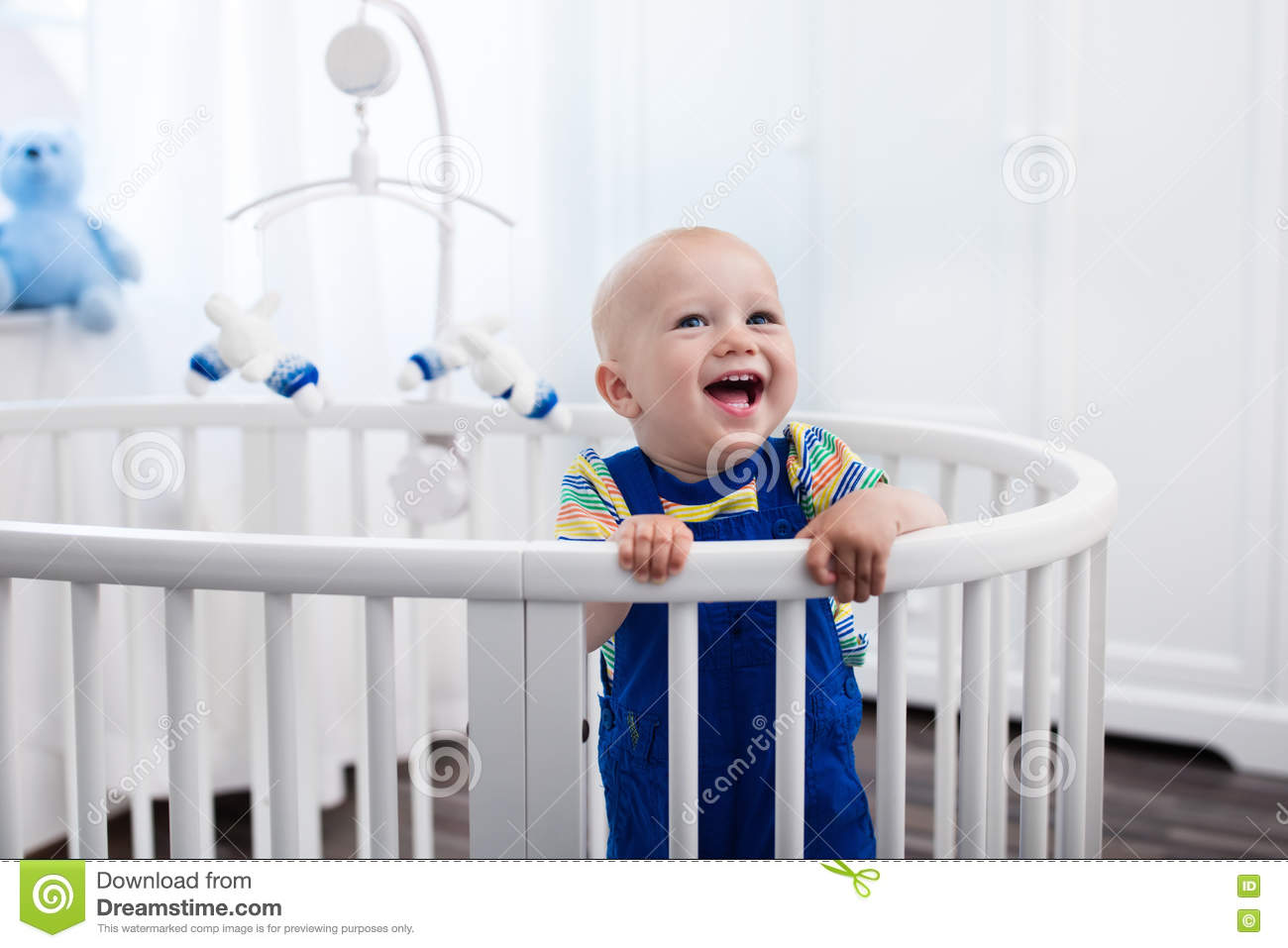 Crib Toys Learning : Baby boy standing in bed stock photo image