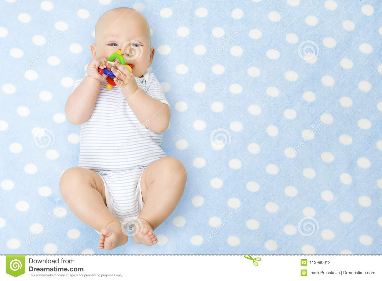 Baby Boy with Teether Toy In Mouth Lying over Blue Background, Happy