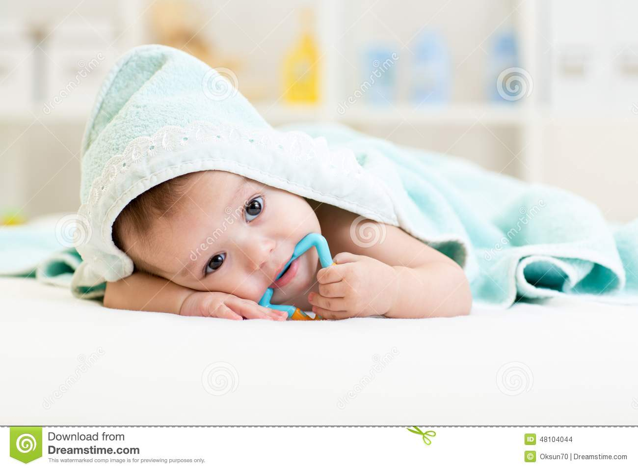 Baby boy under the towel after bathing at home