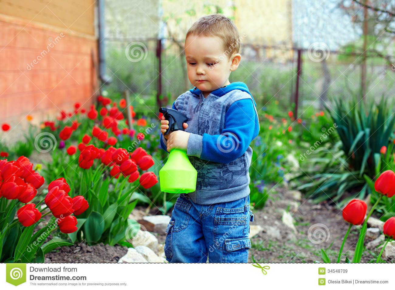 baby boy watering flowers in colorful spring garden stock image