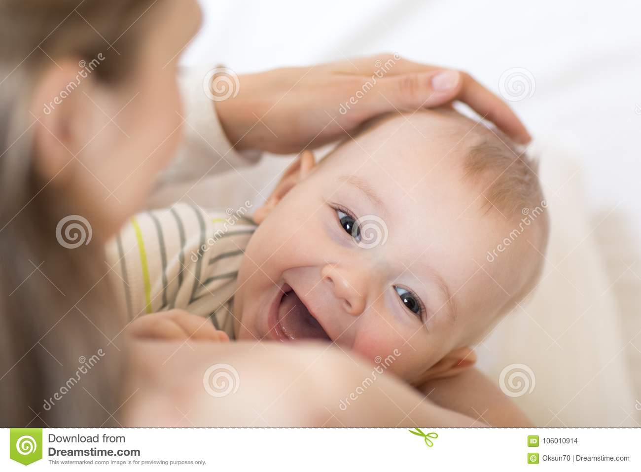 Baby breastfeeding. Mother holding her newborn child. Little kid laughing and looking at camera.