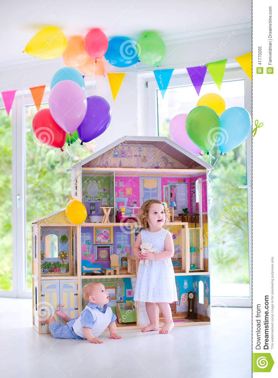 Adorable Curly Toddler Girl In A White Dress And Her Little Baby Brother Playing Together With Birthday Present
