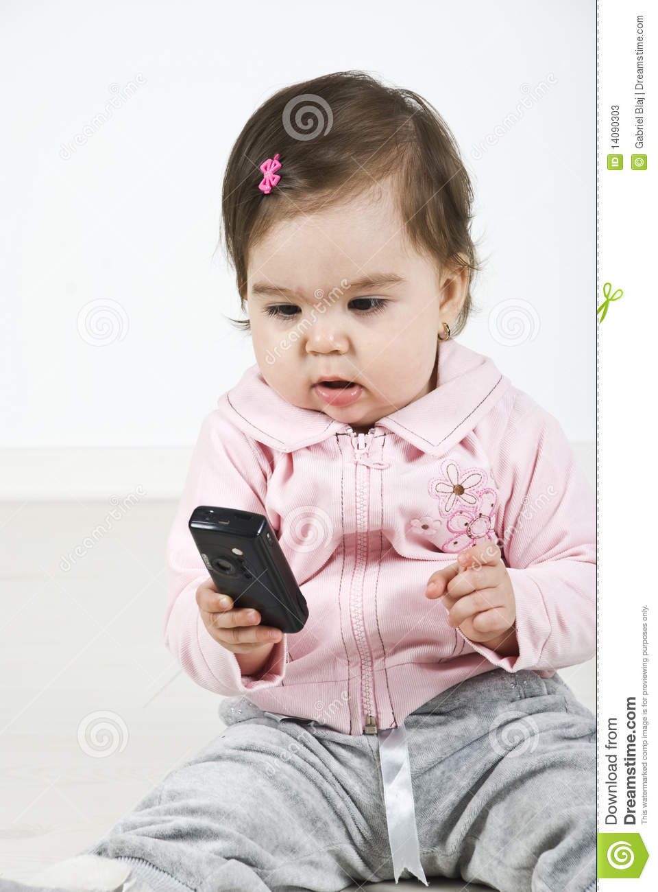 Baby girl holding a phone mobile and sitting on wooden floor check