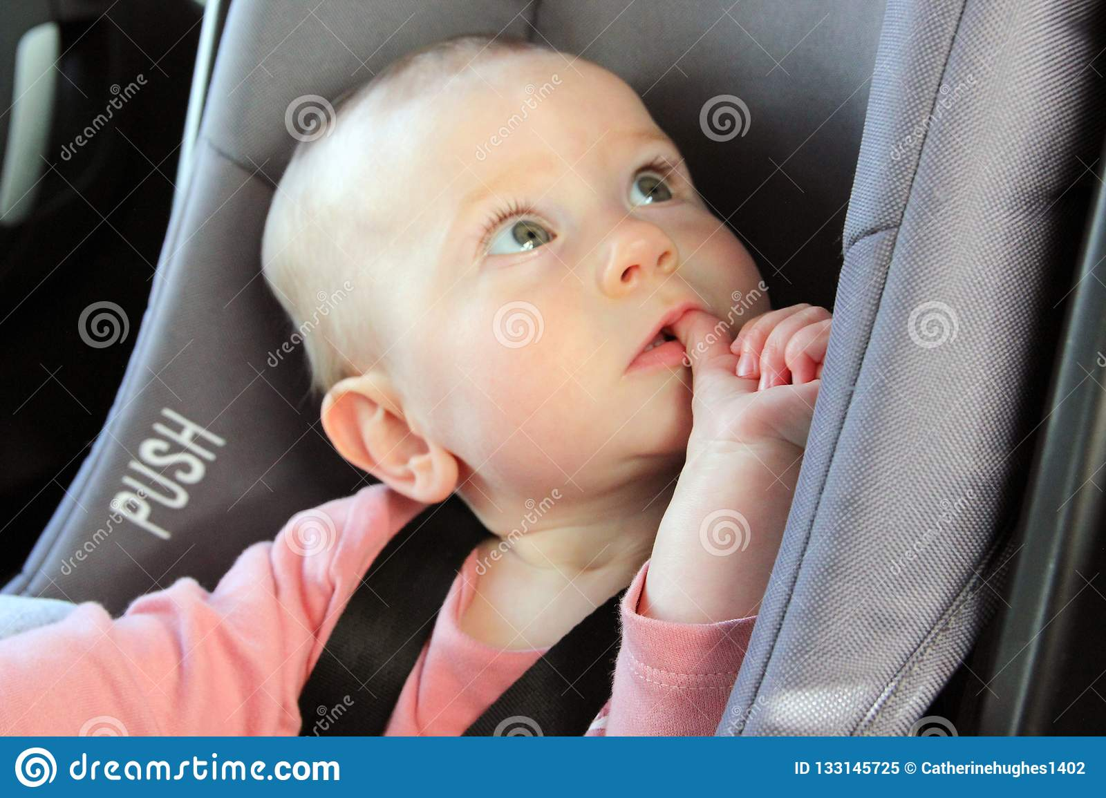 Baby in a car seat looking puzzled