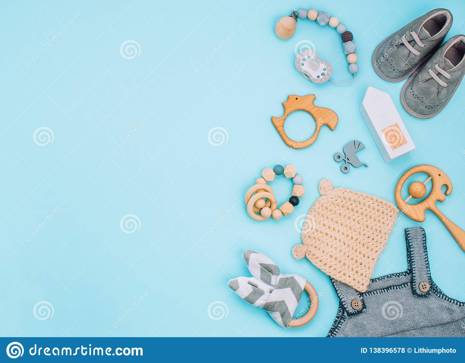Baby Clothes Booties Soother And Wooden Toys On Light Blue Background Stock Photo Image Of Clothes Fashion 138396578