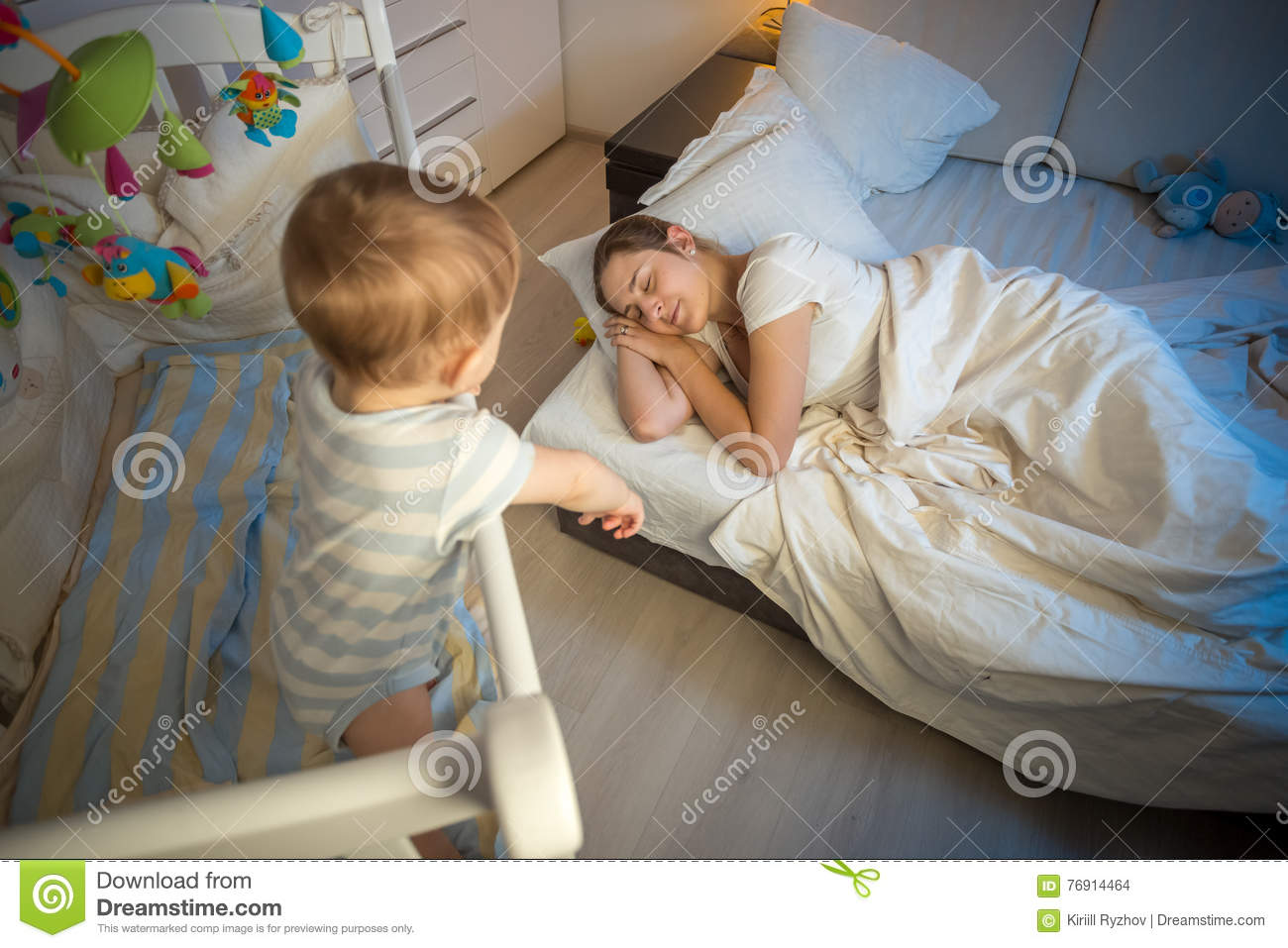 Baby in crib crying and trying to wake up mother that fell asleep