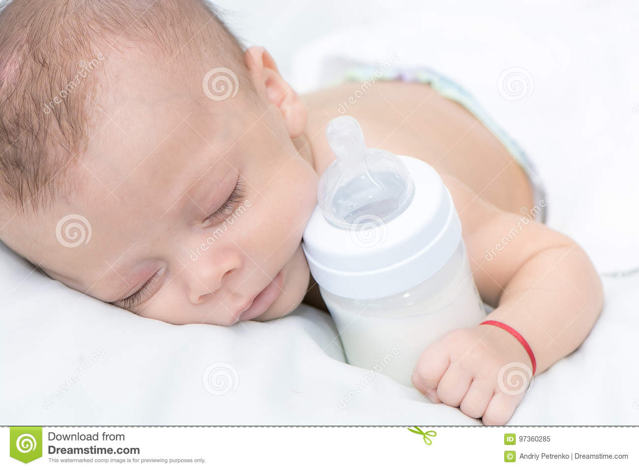 Baby curled up sleeping on a blanket with feeding bottle