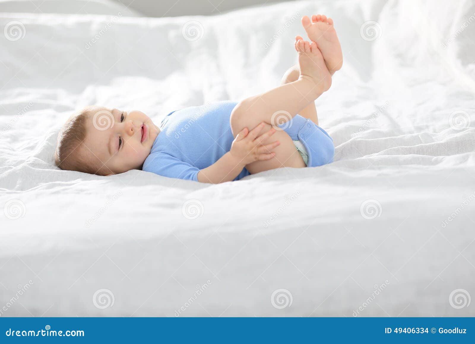 Download Baby, Das Auf Dem Bett Spielt Stockfoto - Bild von glücklich, blau: 49406334