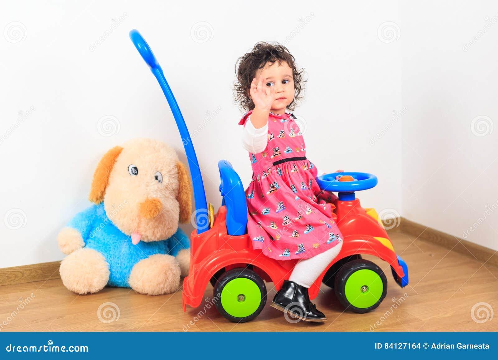 Baby, das auf einem Spielzeugauto zum Abschied winkt