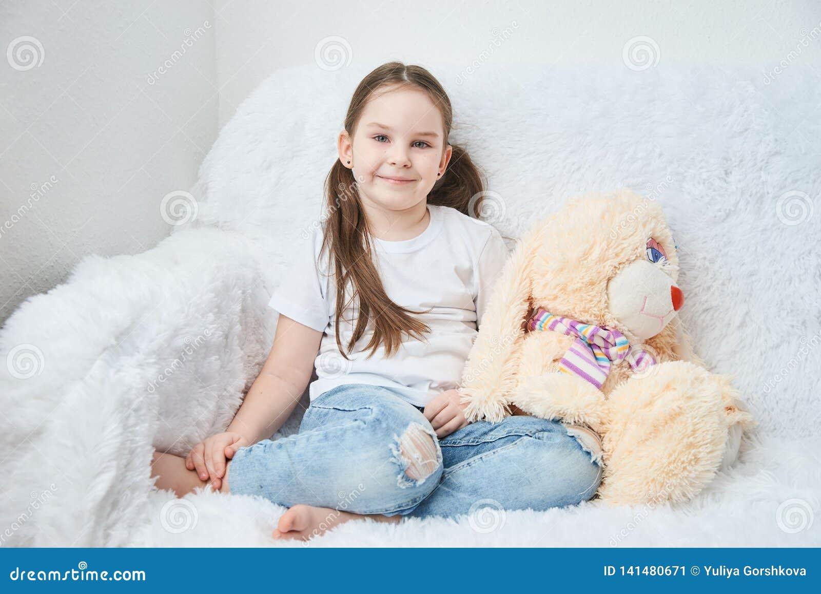 Baby, das auf weißem Sofa in den weißen T-Shirts und in den Blue Jeans sitzt Weicher Plüsch banny