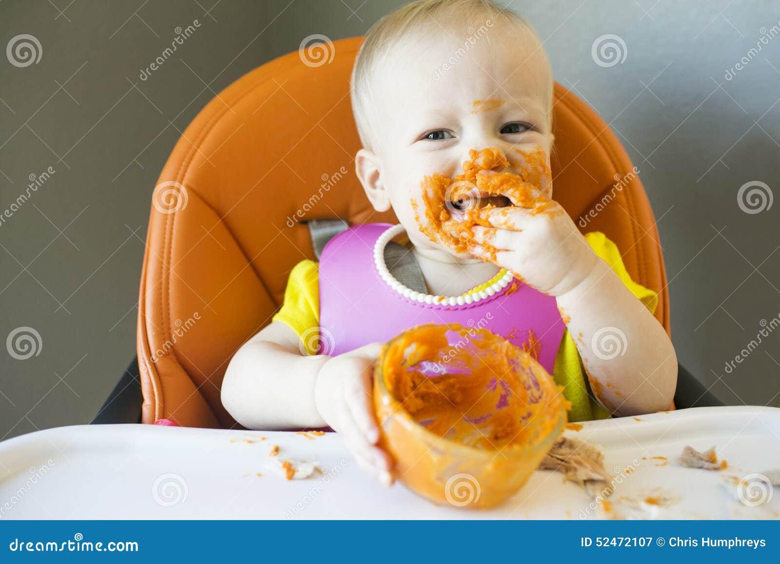 Baby Das Mit Lebensmittel Auf Gesicht Isst Stockbild