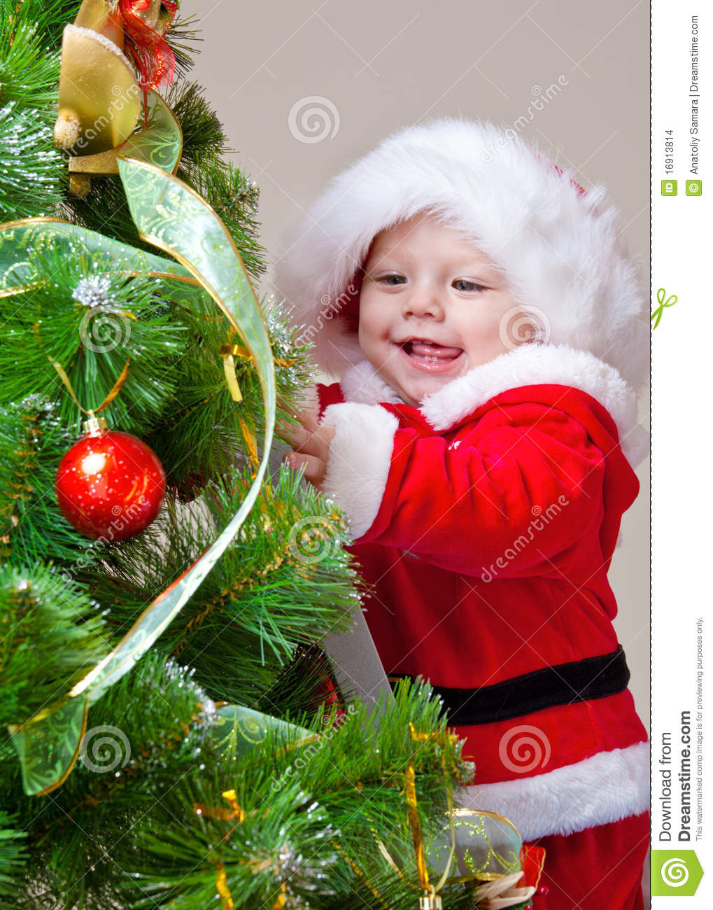 Baby decorating christmas tree stock images image 16913814 for Baby christmas tree decoration