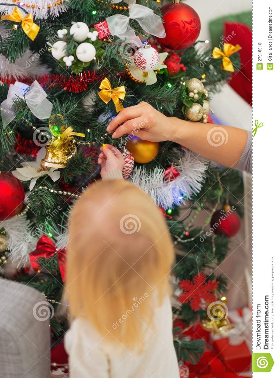Baby decorating christmas tree rear view stock photo for Baby christmas tree decoration
