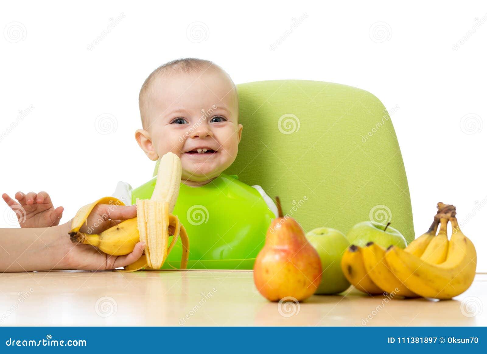 Baby die een lijsthoogtepunt van gezond voedsel hebben Vrolijke peuter met vruchten appelen, bananen, peer Geïsoleerd op wit