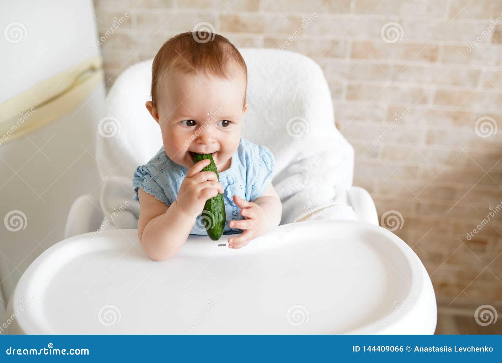 Baby die groenten eten de groene komkommer in meisje dient zonnige keuken in Gezonde voeding voor jonge geitjes Stevig voedsel vo