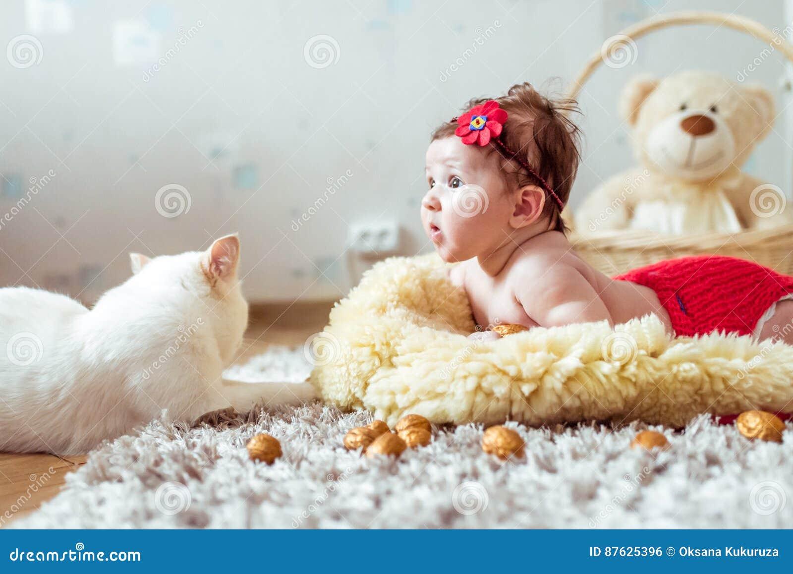 Baby Die Op Een Deken Liggen En Op Een Kat Kijken Stock