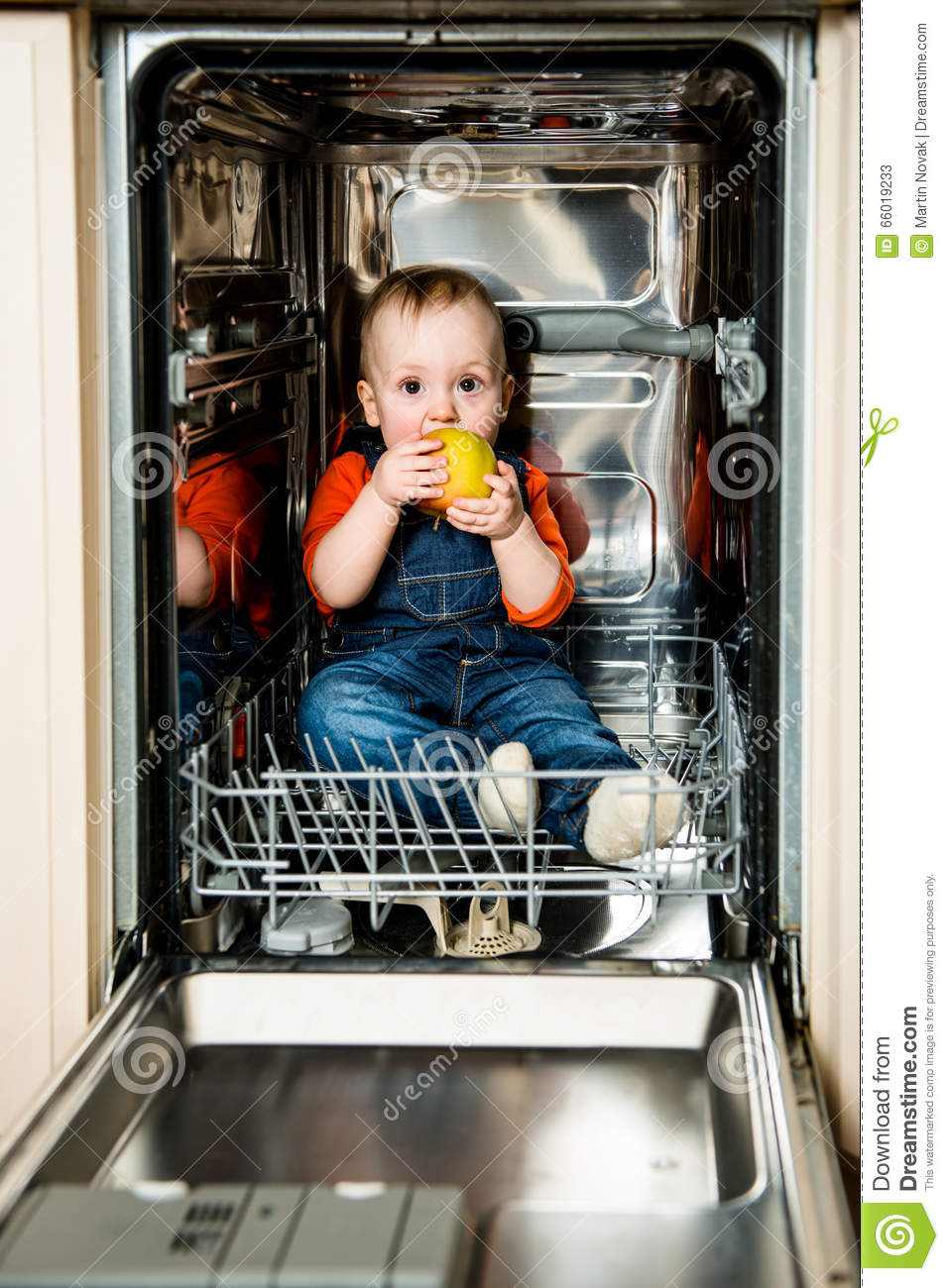 Download Baby Eating Apple In Dishwasher Stock Image