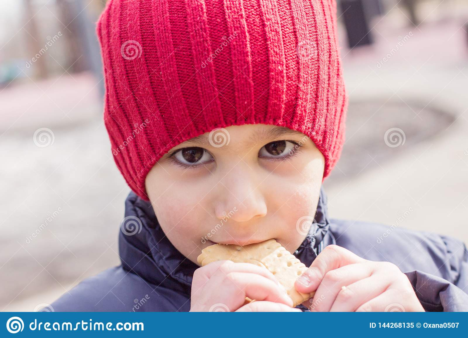 Baby eating cookies outdoors. emotional close-up portrait.