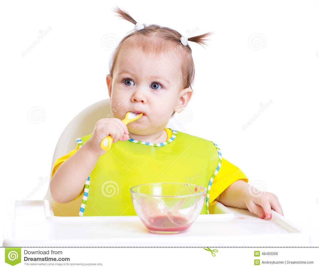 Baby eating with spoon sitting at table