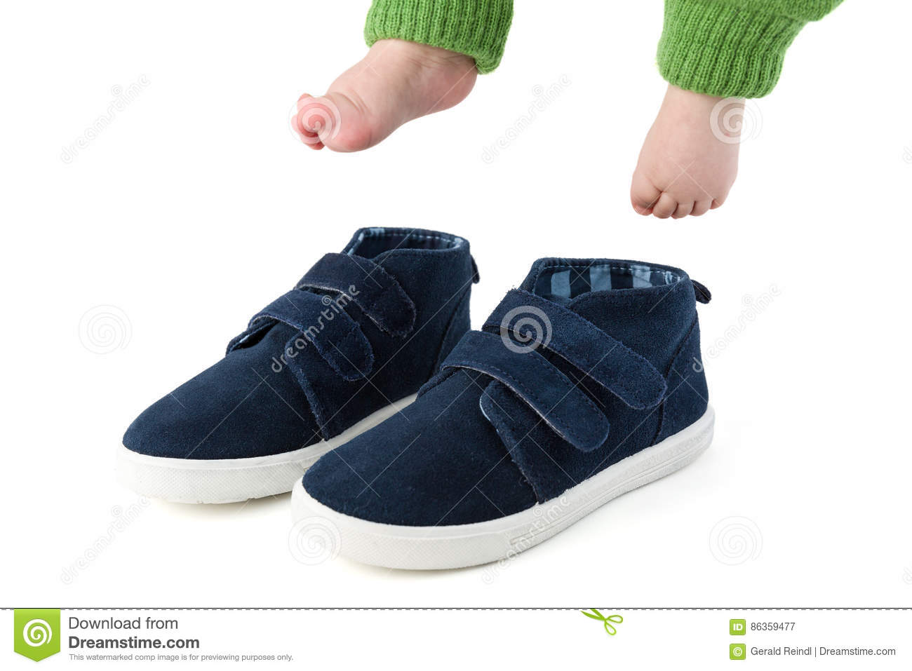 Baby feet with too big blue child shoes isolated on white