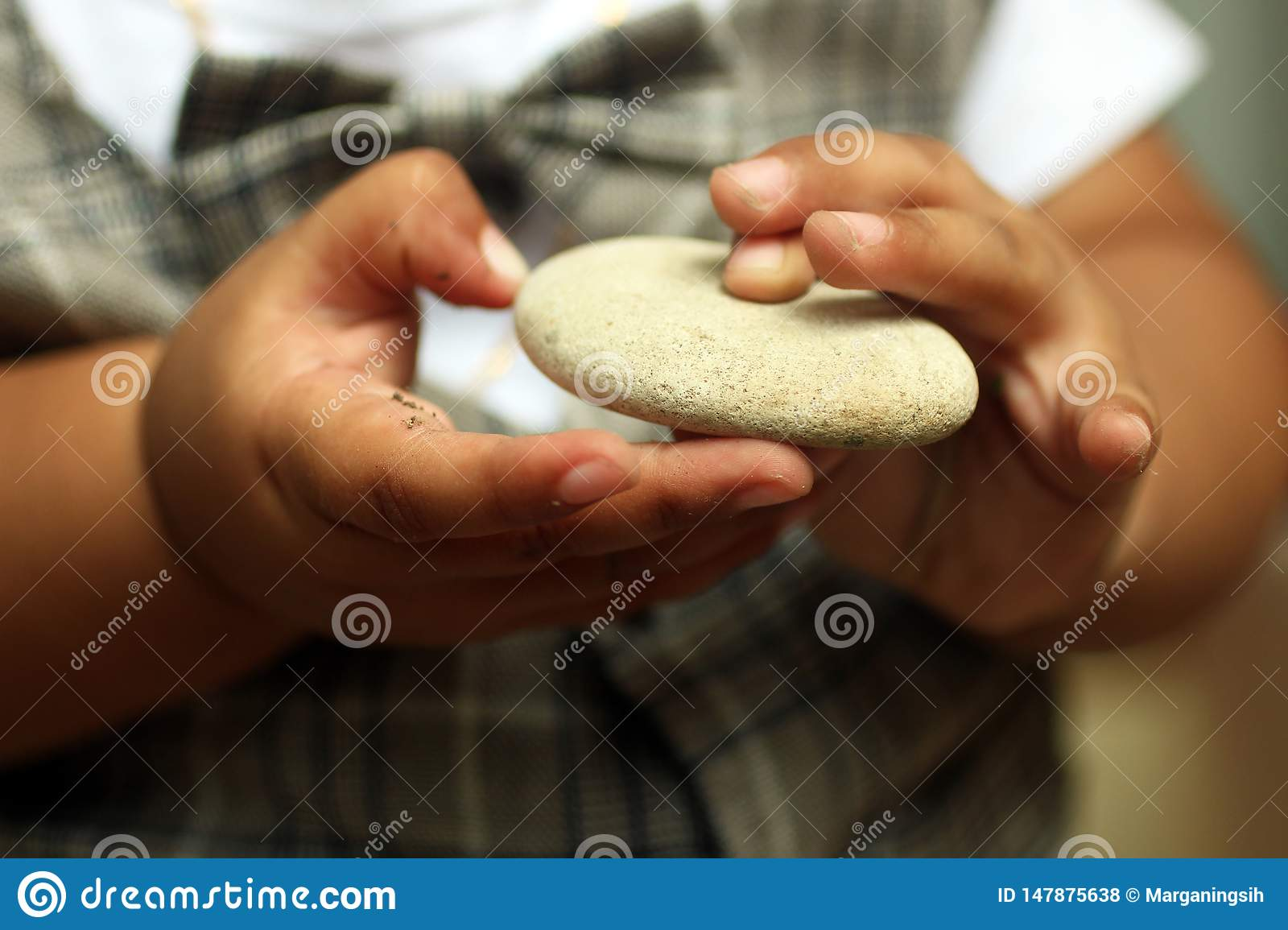 Baby fingers holding white stone. Hands of 1 year old baby
