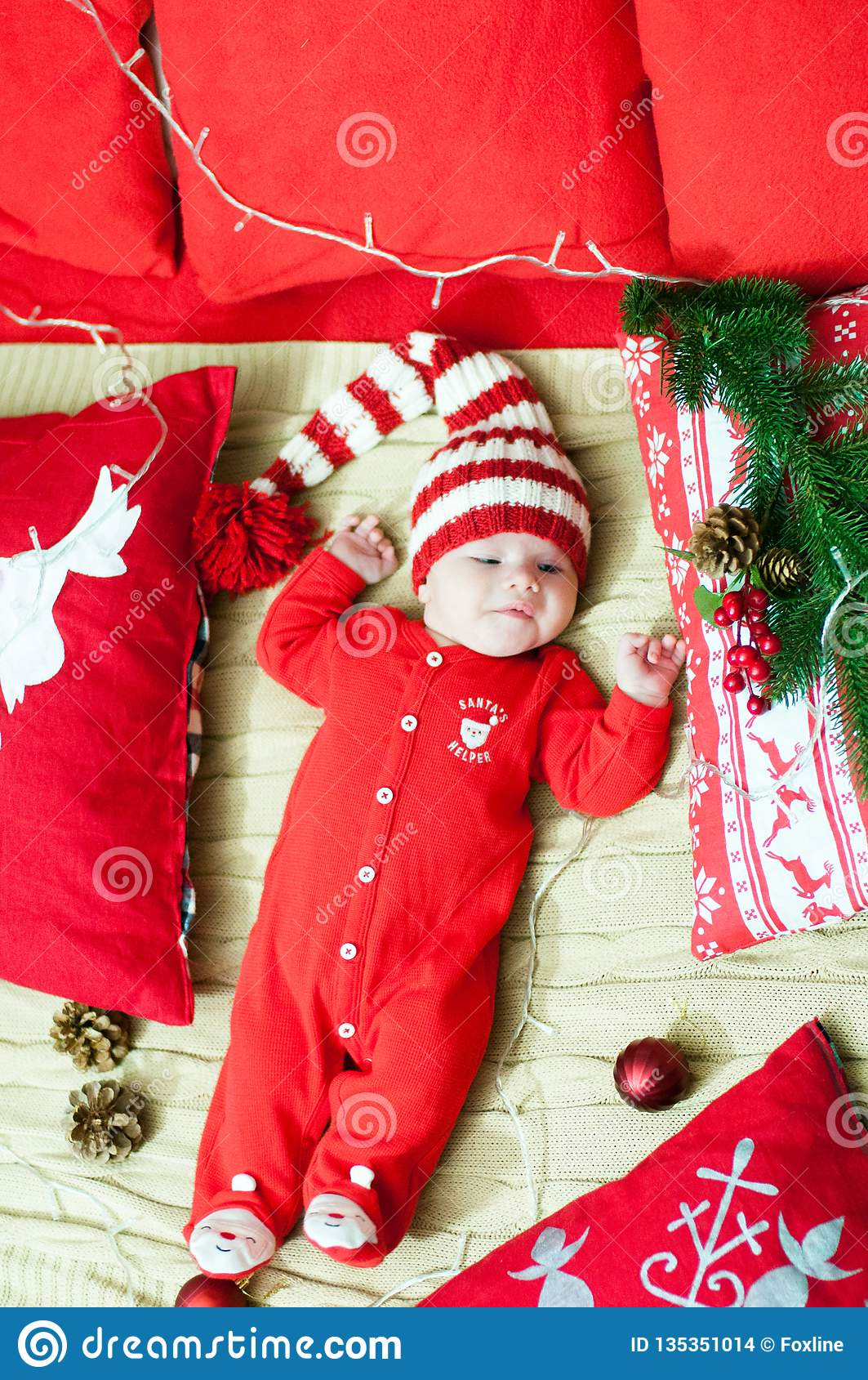 Baby first christmas. Beautiful little baby celebrates Christmas. New Year`s  holidays. Baby with santa hat with gift. 4d276fca8cea