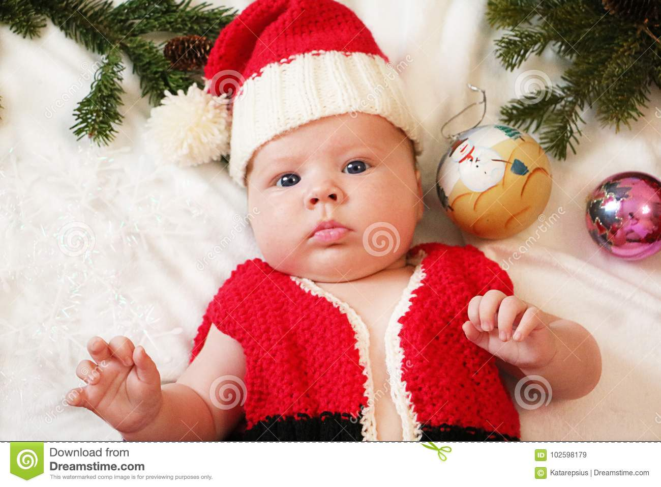 Baby first christmas. Beautiful little baby in Santa hat celebrates  Christmas. New Year`s holidays. Baby with santa hat inside tinsel 274f5652408d