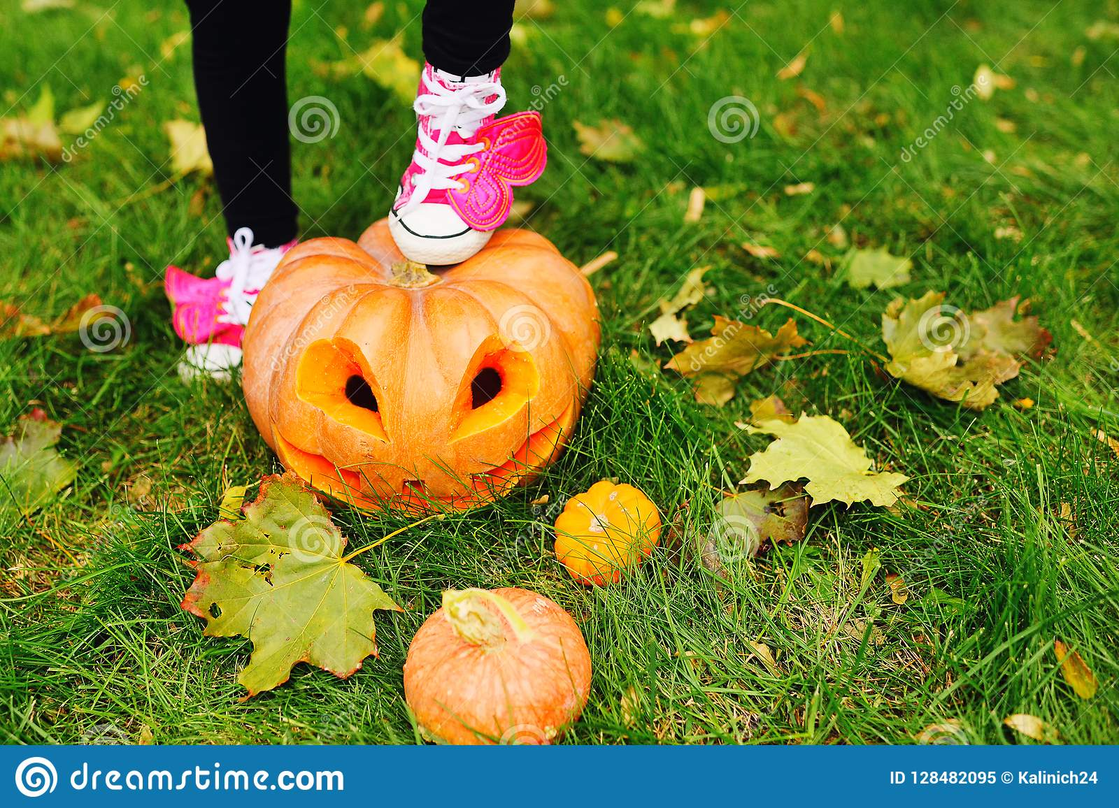 dfa58bf93c3ad Foot In Pink Shoes Is Standing On A Pumpkin With Carved Eyes On ...