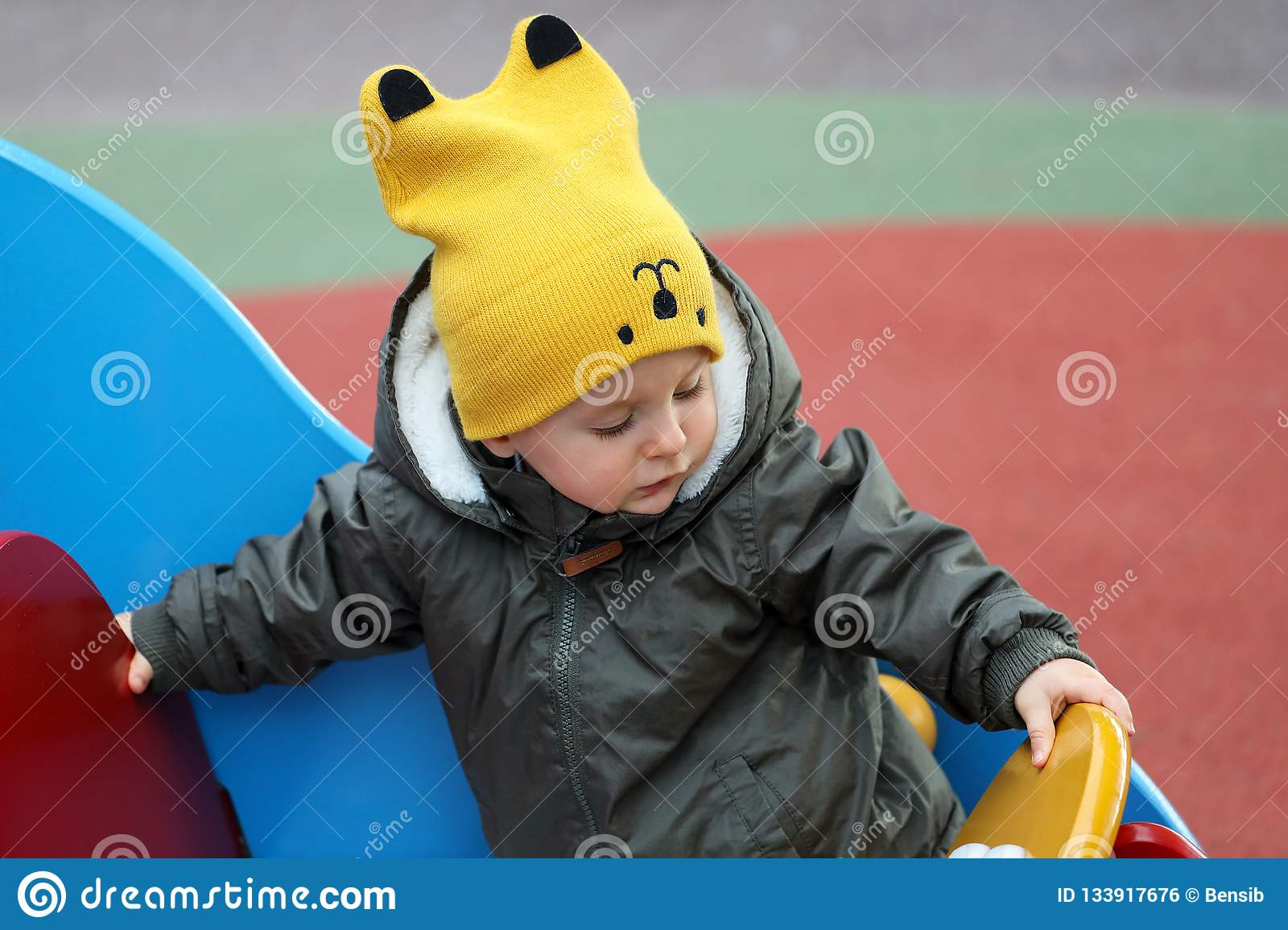 c45364f5ec1 Baby With A Funny Yellow Hat And A Winter Jacket Stock Photo - Image ...