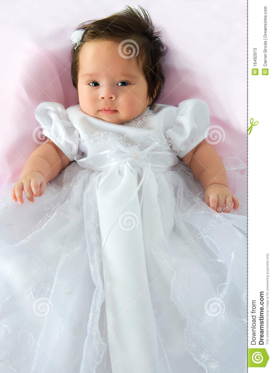 Newborn baby girl in a white baptism dress on a pink blanket.