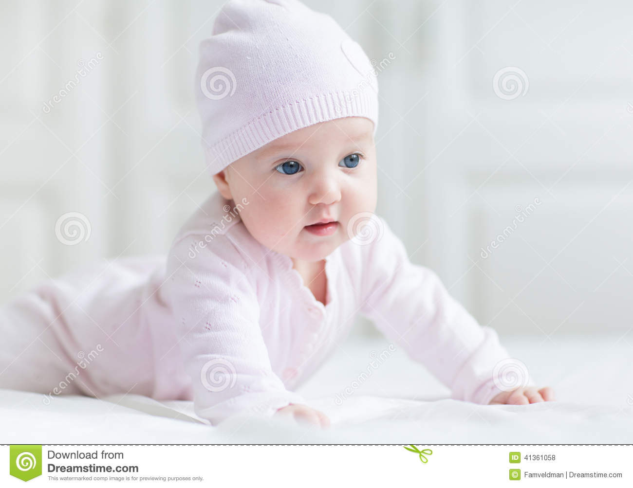 Baby Girl With Big Blue Eyes On White Blanket Stock Photo