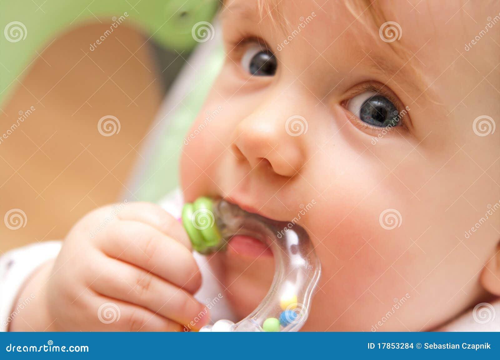 Baby girl biting toy