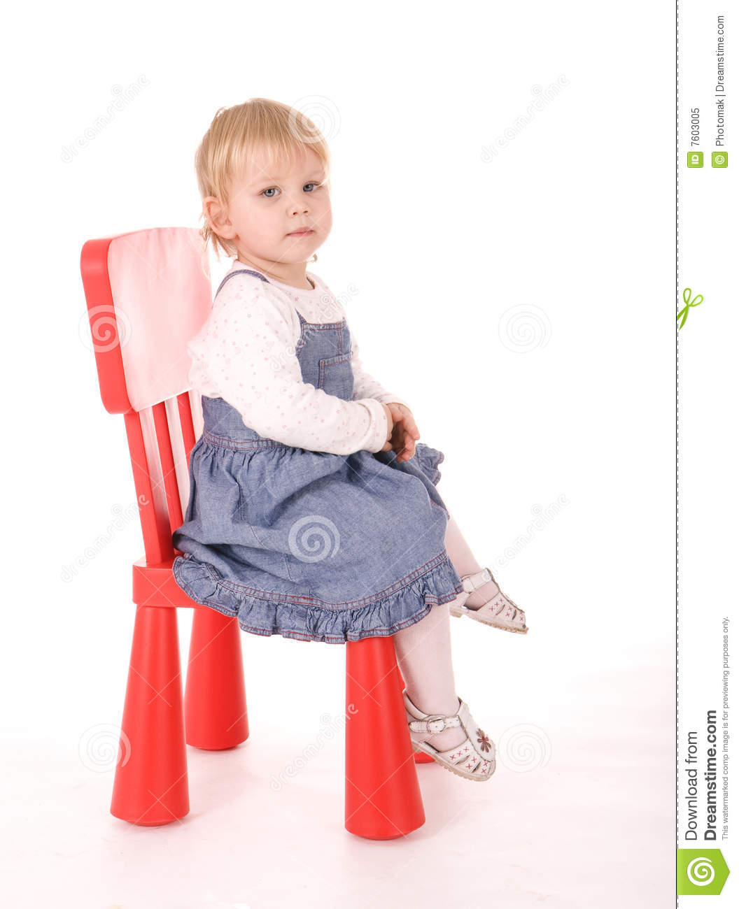 baby girl in blue skirt sitting on chair royalty free