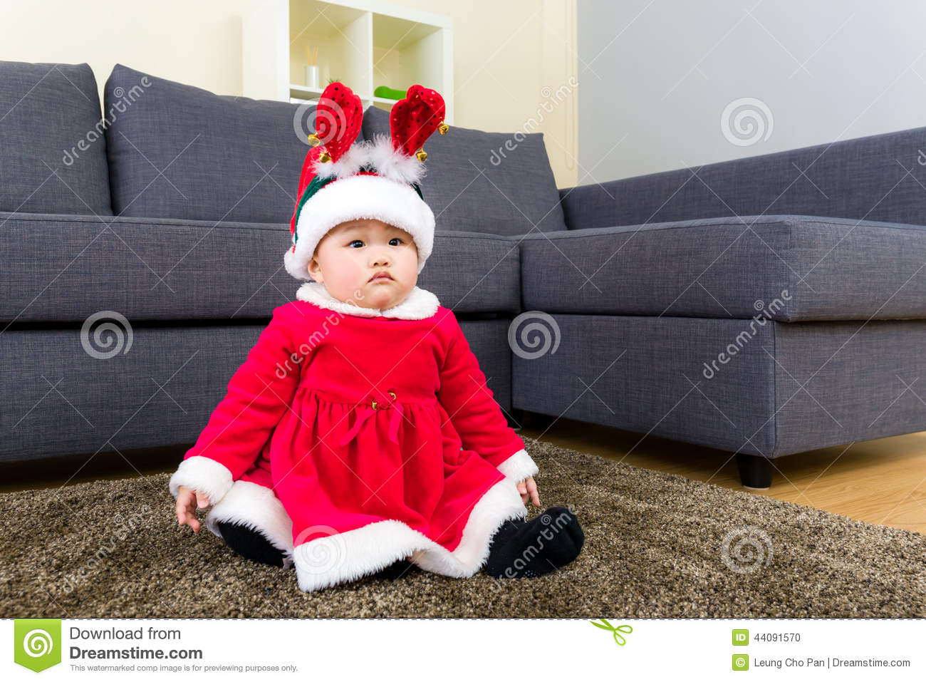 Baby girl with christmas dressing and seating on carpet