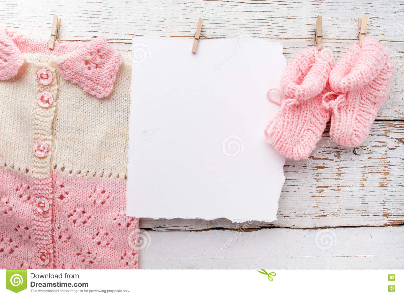 c5d3555a74e4 Baby girl clothes with blank card on white wooden background. Flat lay.  Owerhad view