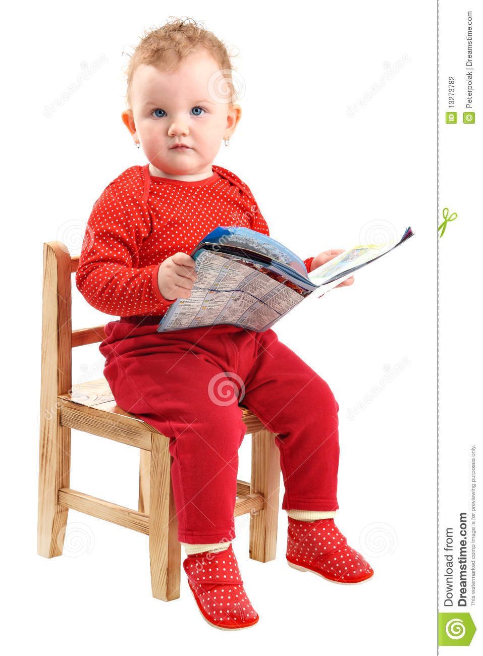 Baby girl dressed in red sitting on chair reading stock for Toddler sitting chair
