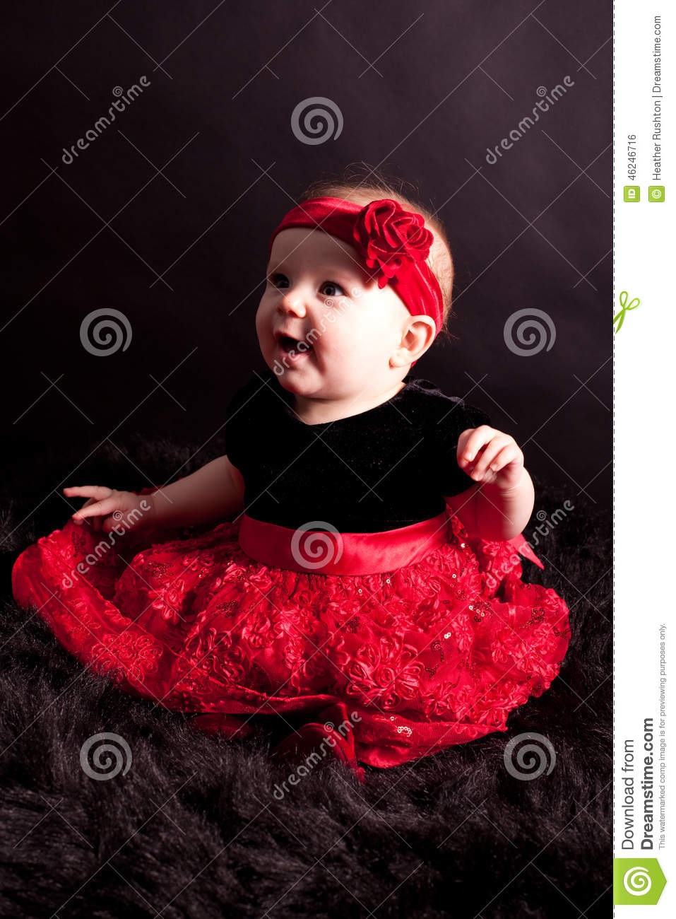 Portrait of smiling baby girl in special outfit of dark t shirt and full red  skirt and matching red hair band b5c5ac9f968