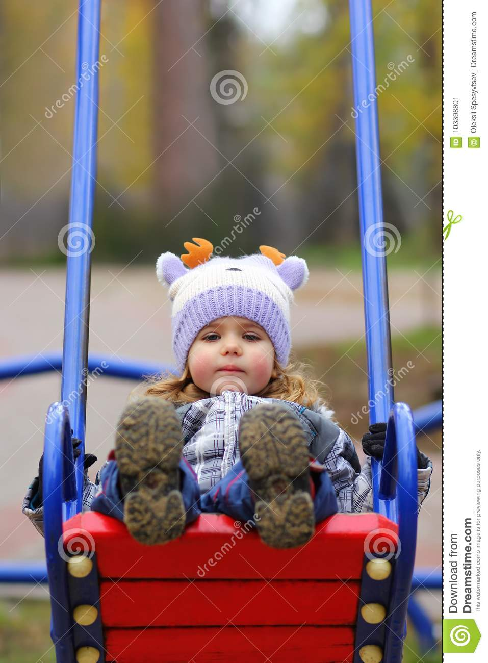 Baby girl in a funny hat swinging on the winter playground, perspective point of view.