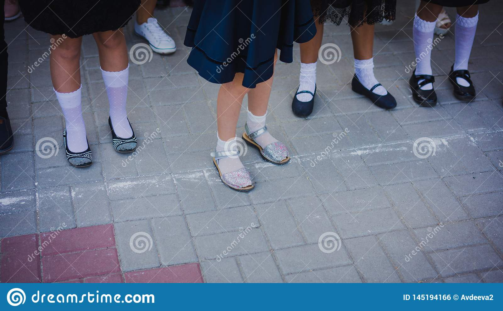 Baby girl legs in white golf and beautiful shoes are in the lineup on the school line on September 1. September 1 - line