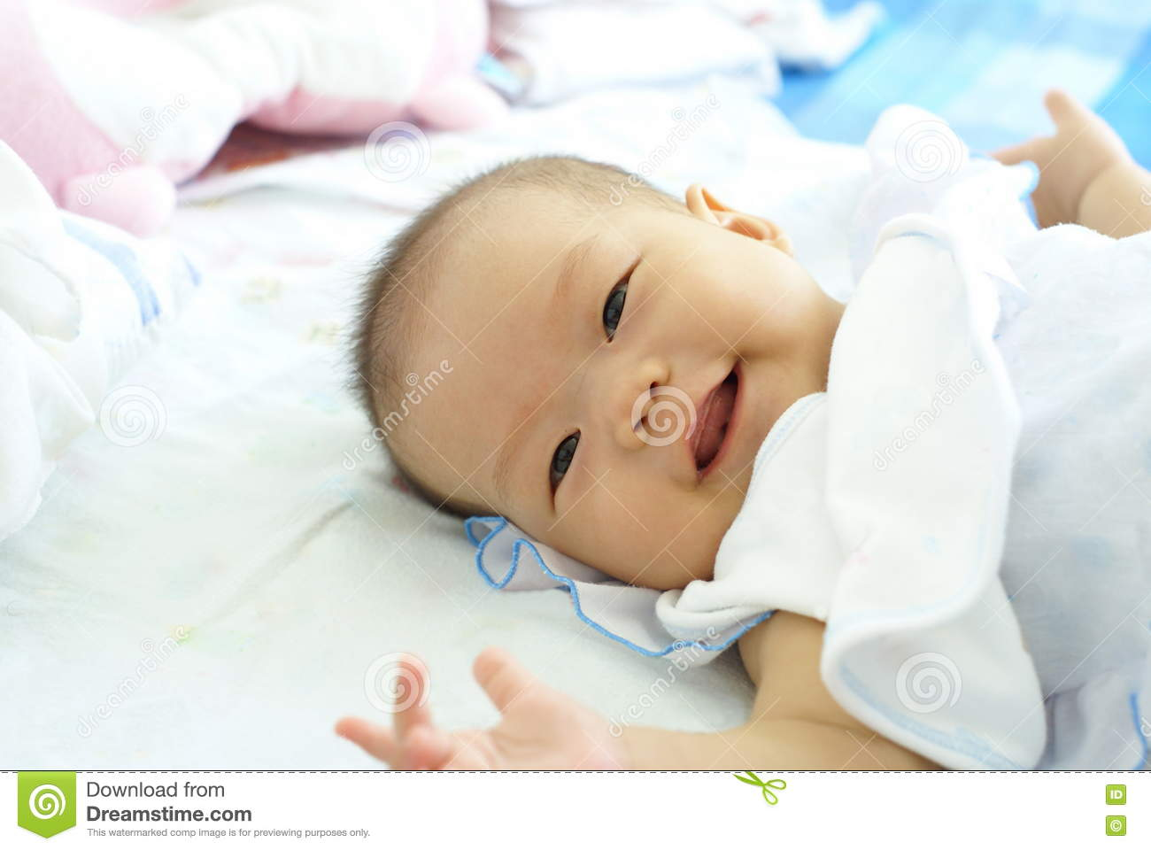 8b97a2c08 Baby Girl Lying On Her Bed. Cute Baby In White Dress Is Smiling ...