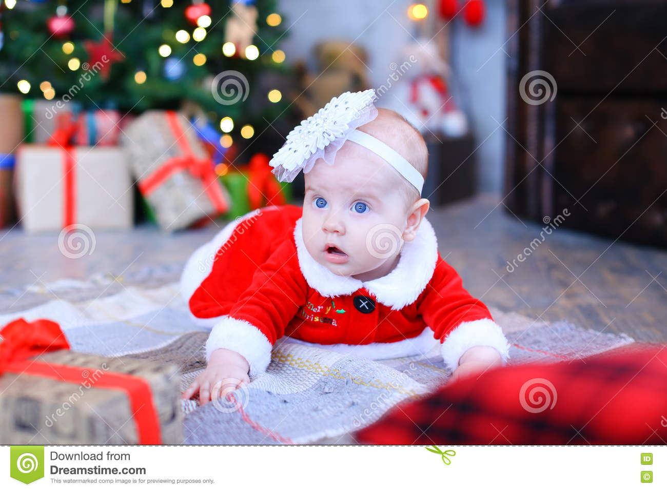 bc7dcb8ea Little infant girl lying on plaid in red dress and white rim with flower on  head on background luminous Christmas tree and boxes with gifts.