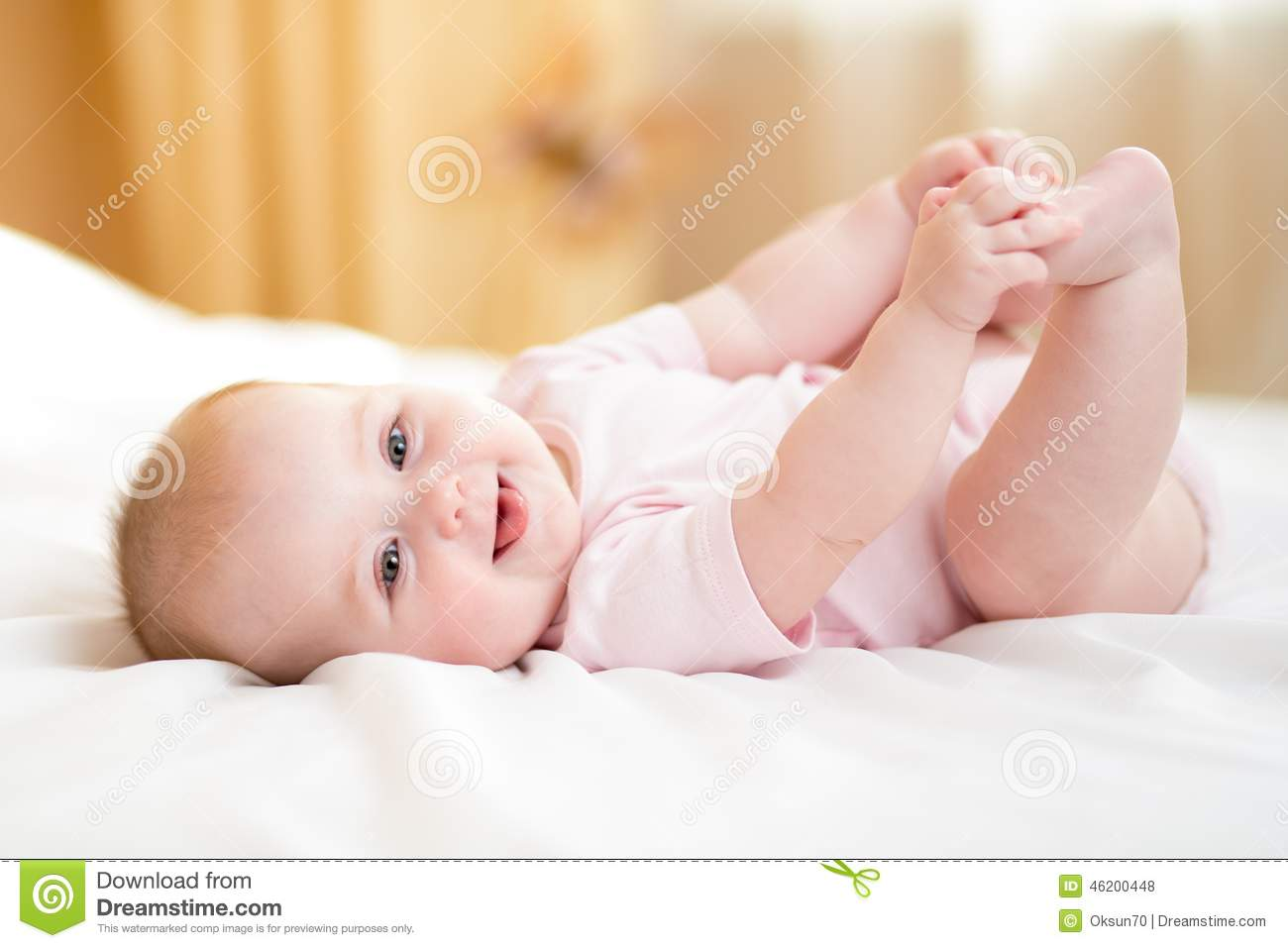 6 Month Old Baby Lying On His White Bed Playing With His