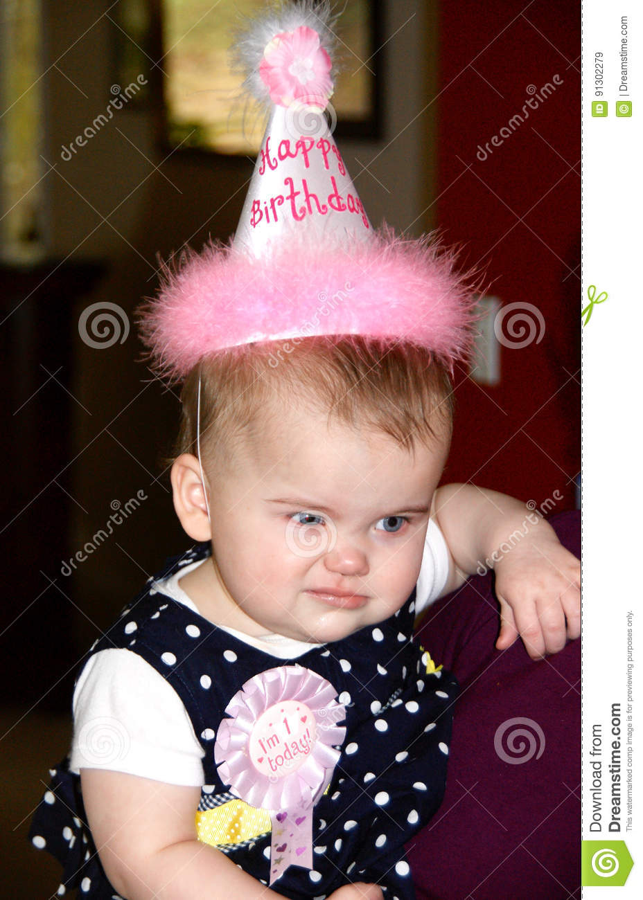 A Baby Girl Is Wearing Happy Birthday Hat And Making Funny Facial Expression During Her First Party Face Showing Anger Or Disgust