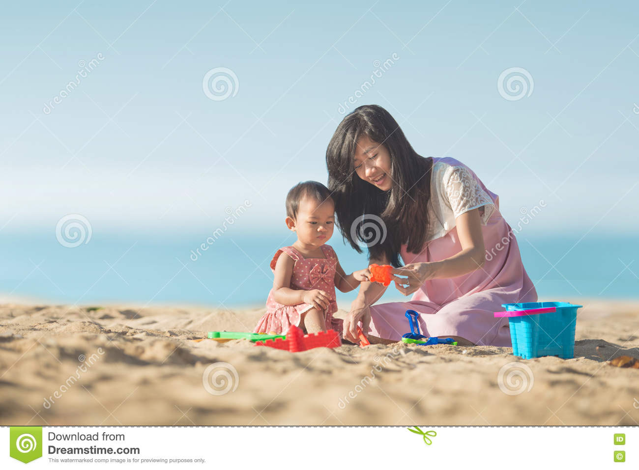 Baby Girl With Mother At The Beach Play With Toys On The