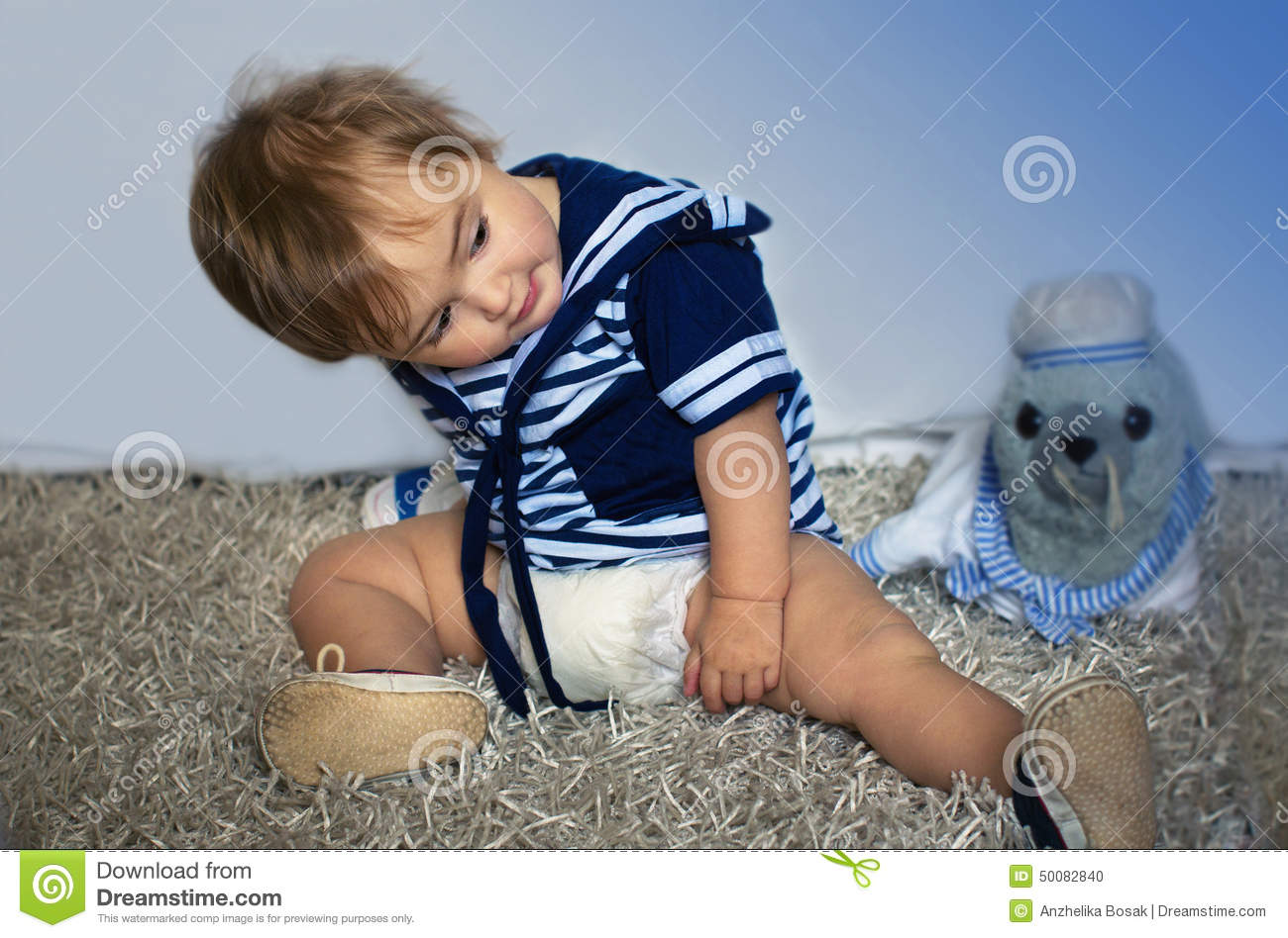 Baby girl in the nautical striped vest sits on the carpet