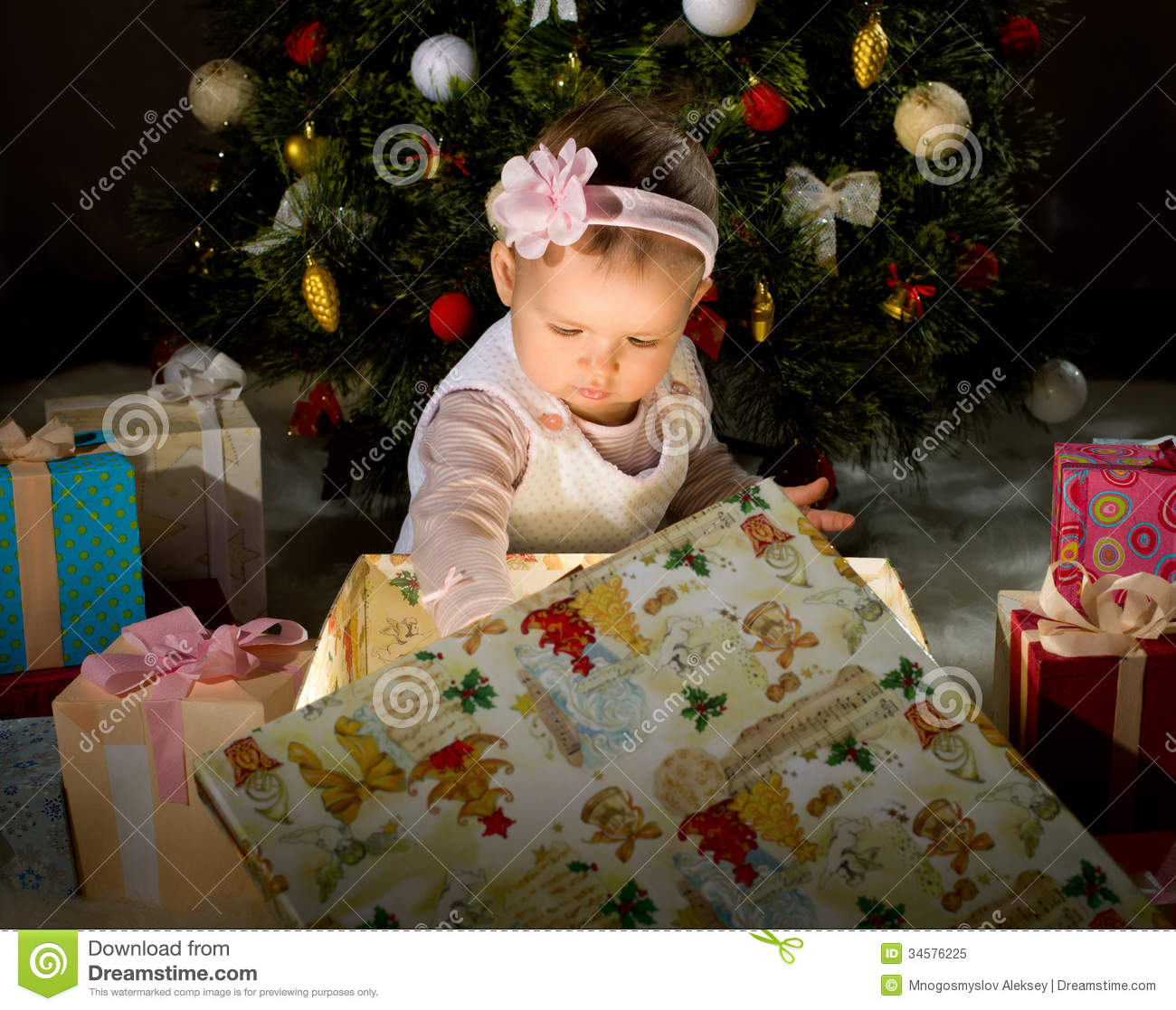 one year old little girl solemnize christmas sit under christmas tree and reach gift of box horizontal photo