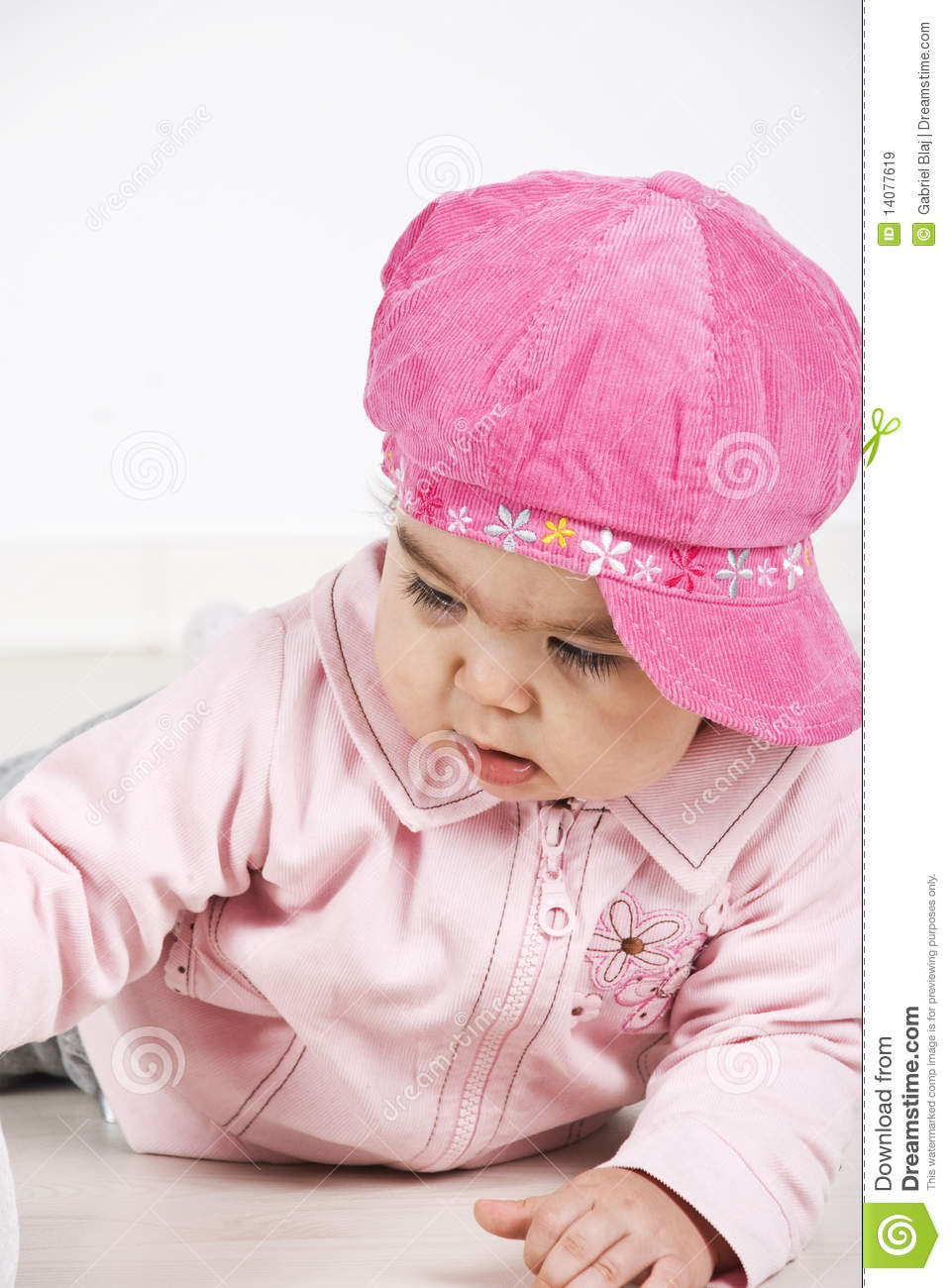 Baby girl with pink cap lying down