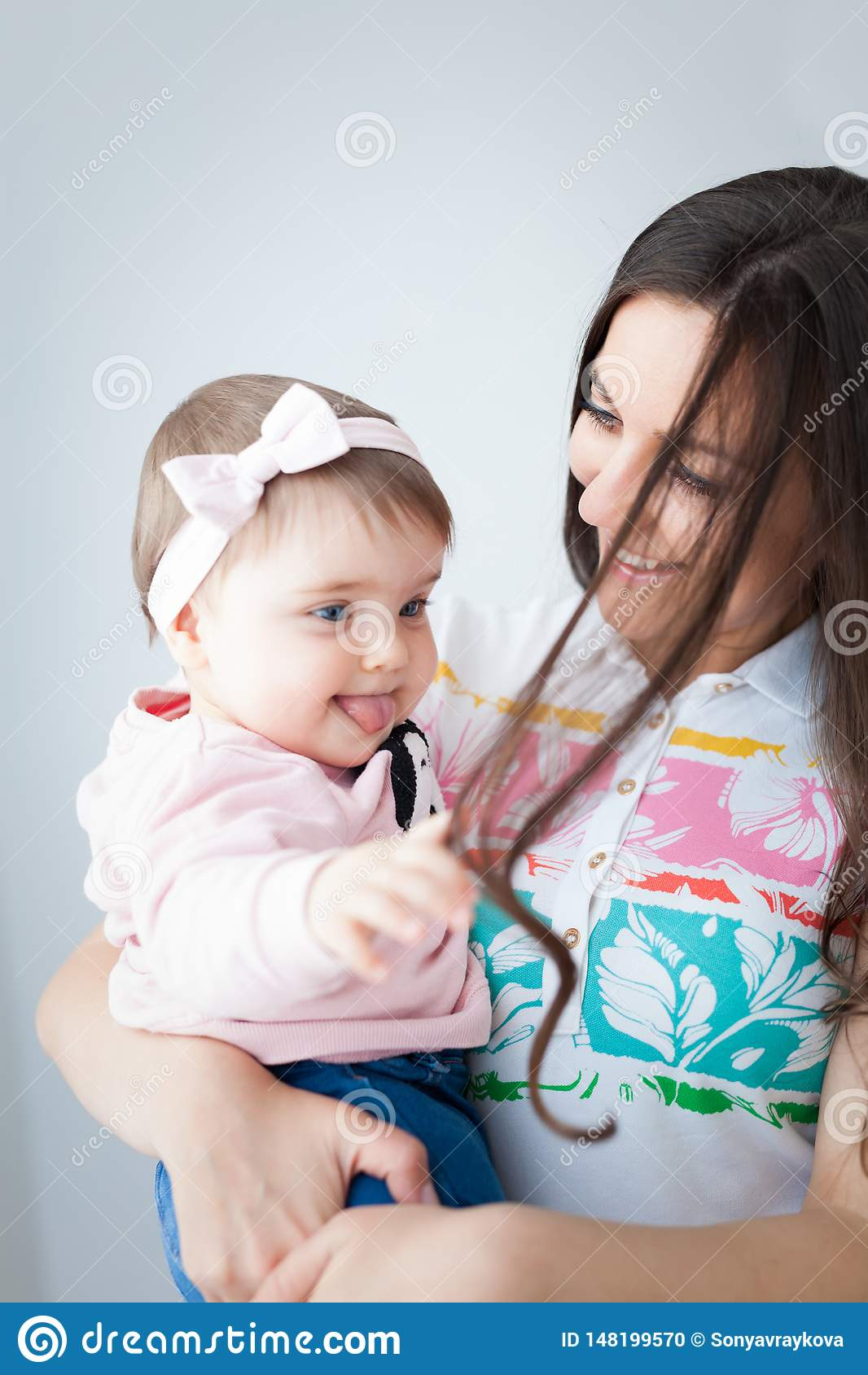 Baby girl playing with her mom`s hair