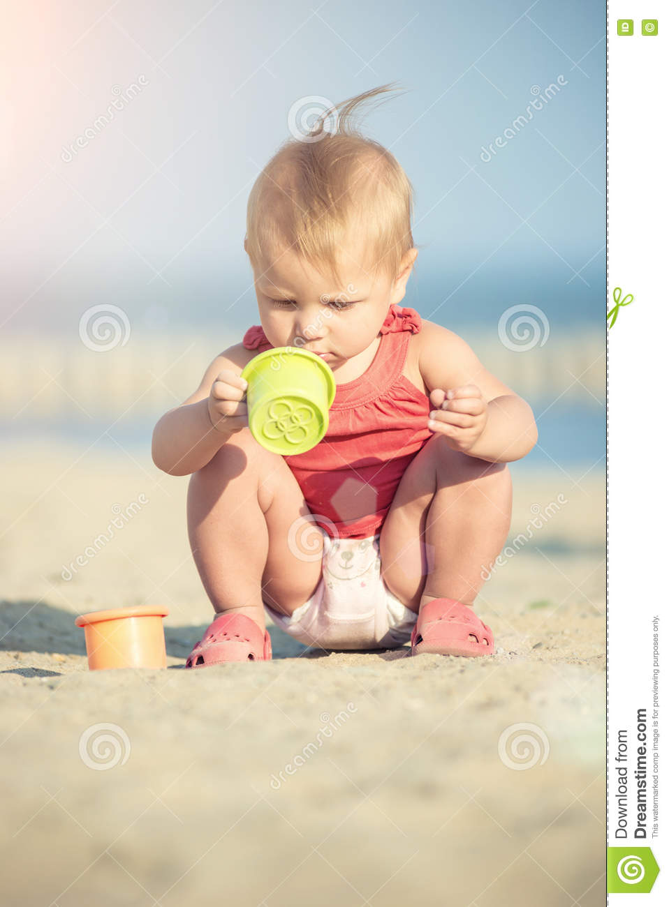 Baby Girl In Red Dress Playing On Sandy Beach Near The Sea