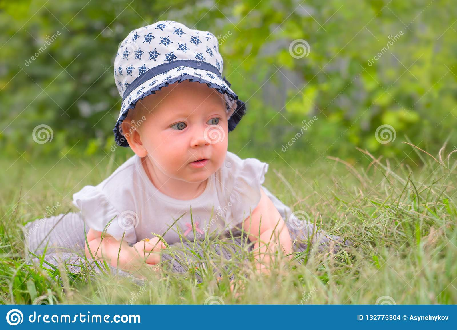 Happy childhood concept. Baby girl in hat, panama. Toddler lying in the grass.
